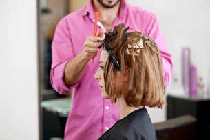 A hairdresser putting foils in a female clients hairの写真素材 [FYI02122371]