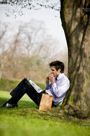 A businessman leaning against a tree, eating a sandwich and reading the newspaperの写真素材 [FYI02122373]