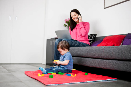 A mother using a laptop and talking on the phone, baby son playing at her feetの写真素材 [FYI02122377]