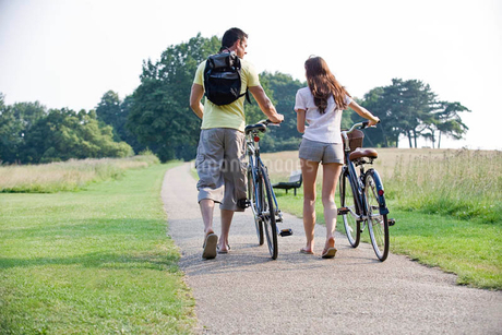 A young couple pushing bicycles uphillの写真素材 [FYI02122397]