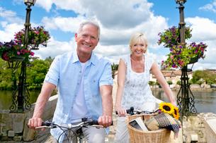Portrait Of Mature Couple Riding Cycle Over Bridgeの写真素材 [FYI02122404]