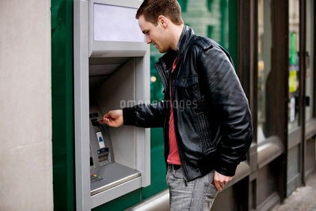 A young man using a cash machineの写真素材 [FYI02122405]