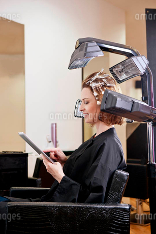 A female client using an digital tablet whilst she has her hair coloured in a hairdressing salonの写真素材 [FYI02122413]