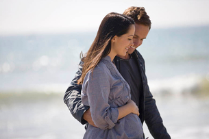 A pregnant woman and her partner walking on the beachの写真素材 [FYI02122416]
