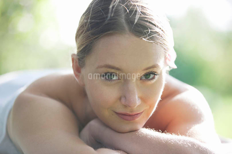 A young woman laying on a massage table, looking to cameraの写真素材 [FYI02122422]