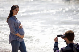 A young man filming his pregnant partner on the beachの写真素材 [FYI02122423]