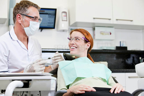 A male dentist talking to a female patientの写真素材 [FYI02122426]