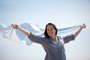 A pregnant woman holding a scarf into the windの写真素材 [FYI02122427]