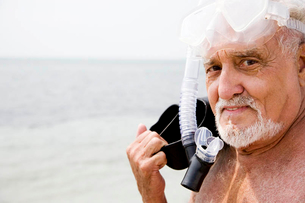 Senior man with snorkel gear and flippers at the beachの写真素材 [FYI02122449]