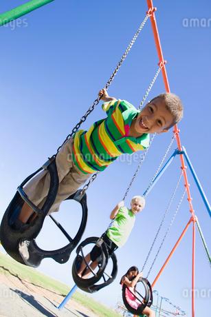 Children on swing set at playgroundの写真素材 [FYI02122478]