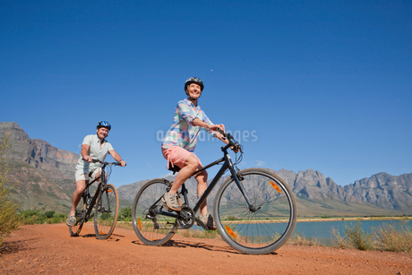 Senior couple mountain biking on country trackの写真素材 [FYI02122481]