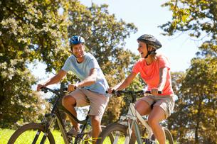 Couple riding mountain bikes in rural fieldの写真素材 [FYI02122487]