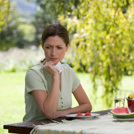 A woman looking sad and pensive sitting in the gardenの写真素材 [FYI02122496]