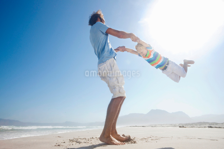 Father swinging son in the air playfully on sunny beachの写真素材 [FYI02122498]