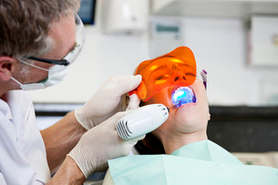 A male dentist filling a female patients teethの写真素材 [FYI02122500]