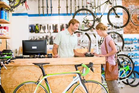Store manager assisting customer in bicycle shopの写真素材 [FYI02122518]