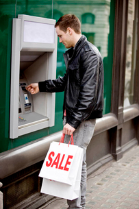 A young man using a cash machine, holding carrier bagsの写真素材 [FYI02122519]