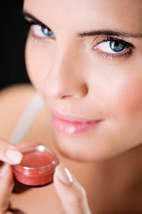 Woman applying lip glossの写真素材 [FYI02122534]