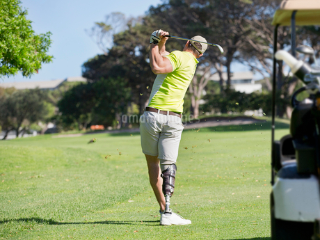 Rear View Of Golfer With Artificial Leg Hitting Ball On Fairwayの写真素材 [FYI02122535]