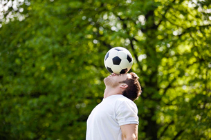 A young man balancing a football on his foreheadの写真素材 [FYI02122558]