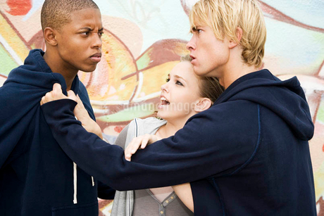 Two men fighting over a girl in front of a graffiti covered wallの写真素材 [FYI02122559]