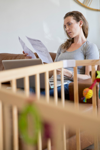 Stressed Mother With Laptop Looking At Household Billsの写真素材 [FYI02122573]