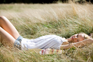 A young woman lying on the grass, asleepの写真素材 [FYI02122581]