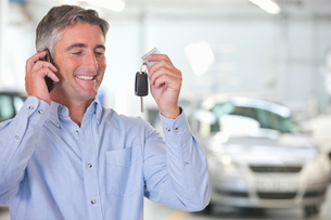 Man on mobile phone holding up car keys of new carの写真素材 [FYI02122599]