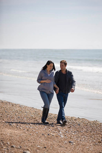 A pregnant woman and her partner walking on the beachの写真素材 [FYI02122610]
