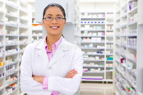 Pharmacist, with arms crossed, smiling at camera in pharmacyの写真素材 [FYI02122615]