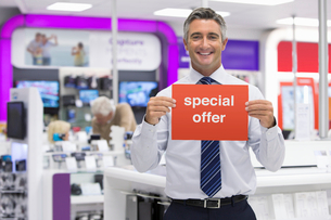 Portrait of smiling salesman holding Special Offer sign in electronics storeの写真素材 [FYI02122620]