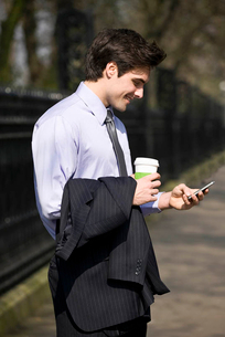 A businessman holding a hot drink, looking at his mobile phoneの写真素材 [FYI02122632]