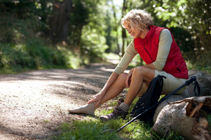 A mature woman resting beside a country path, massaging her sore feetの写真素材 [FYI02122645]