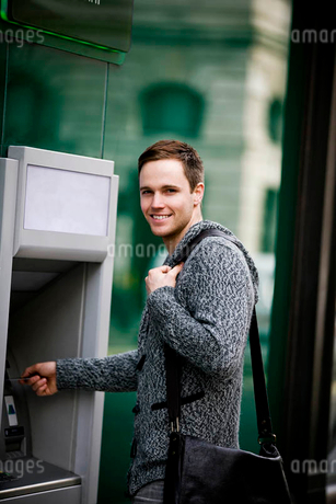 A young man using a cash machineの写真素材 [FYI02122654]