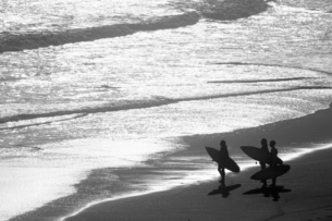Group of Surfers carrying surf boards looking out to seaの写真素材 [FYI02122663]