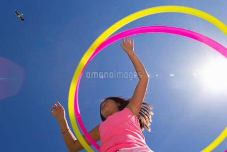 Girl spinning two plastic hoopsの写真素材 [FYI02122667]