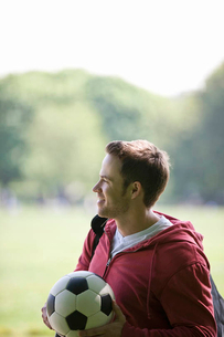 A young man in the park carrying a footballの写真素材 [FYI02122675]