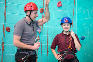 Portrait smiling high school student with gym teacher at rock climbing wallの写真素材 [FYI02122689]