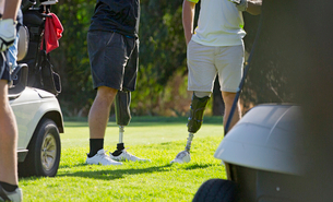 Close Up Of Male Golfers With Artificial Legs Standing By Greenの写真素材 [FYI02122690]