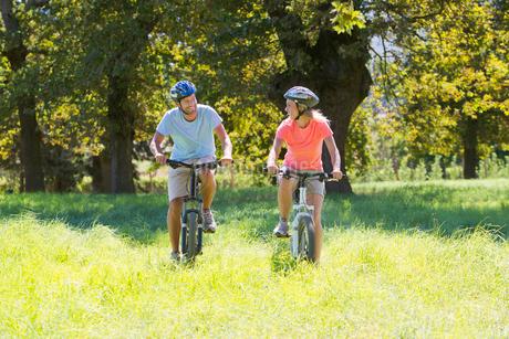 Couple, mountain biking, in treelined fieldの写真素材 [FYI02122696]