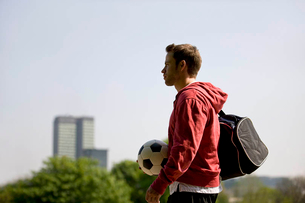 A young man standing in the park, carrying a football and a sports bagの写真素材 [FYI02122706]