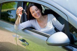 Portrait happy woman in new car holding keysの写真素材 [FYI02122711]