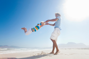 Smiling Father swinging son around playfully on sunny beachの写真素材 [FYI02122715]
