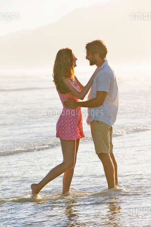 Romantic couple embracing, looking into each others eyes, on sunny beachの写真素材 [FYI02122741]