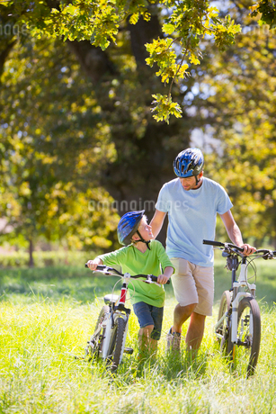 Father and son pushing mountain bikes, in treelined fieldの写真素材 [FYI02122761]