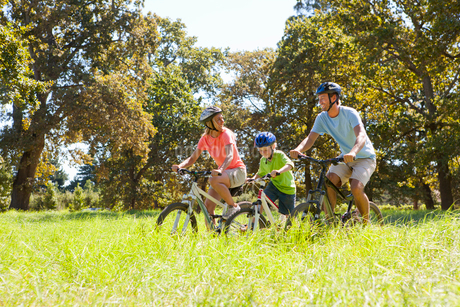 Family riding mountain bikes in rural fieldの写真素材 [FYI02122780]