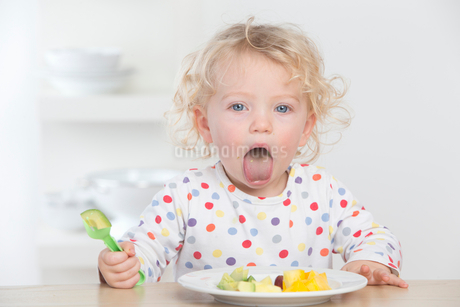 Baby eating fruit making a faceの写真素材 [FYI02122785]