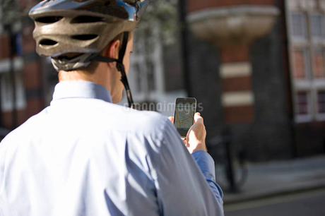 A businessman on his bicycle, looking at a map on his mobile phoneの写真素材 [FYI02122794]