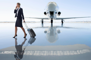 Businesswoman Using Mobile Phone By Private Airplaneの写真素材 [FYI02122803]