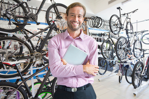 Store owner in bicycle shop smiling at cameraの写真素材 [FYI02122806]